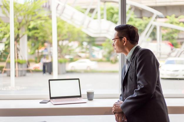 Homme d'affaires d'asie travaillant avec un ordinateur portable assis café-restaurant. concept de jeunes entreprises