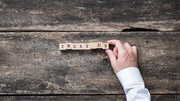 Homme d'affaires, assemblage d'un signe nous faire confiance orthographié sur des blocs de bois.