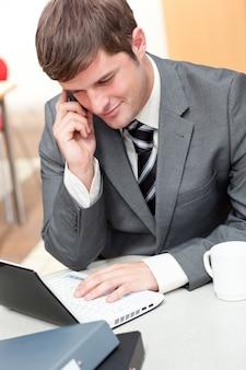 Homme d'affaires assertive, parler au téléphone et en utilisant son ordinateur portable dans son bureau
