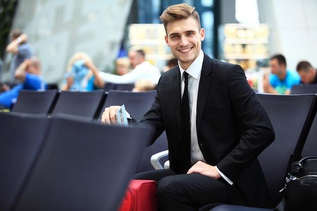 Un homme d'affaires assis à l'aéroport, en attente de vol
