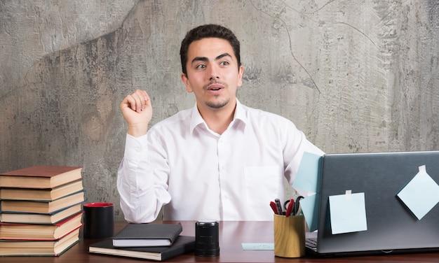 Homme d'affaires assis au bureau avec ordinateur portable, livres et crayons.