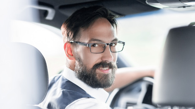 Homme d'affaires assis au volant d'une voiture.
