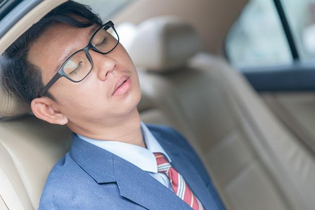 Homme d'affaires assis sur la banquette arrière d'une voiture