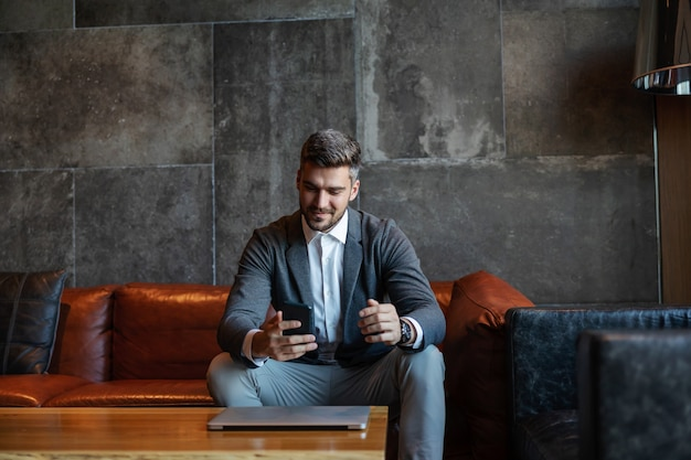 Homme d'affaires assis sur un canapé dans un espace moderne unique et utilisant le téléphone et un ordinateur portable.