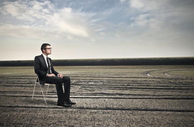 Homme d'affaires assis sur une chaise au milieu de nulle part