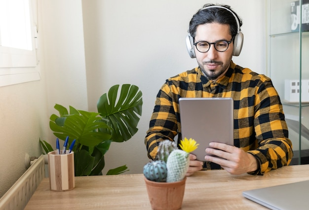 Homme d'affaires assis dans un bureau décoré utilise une tablette tout en écoutant de la musique avec des écouteurs