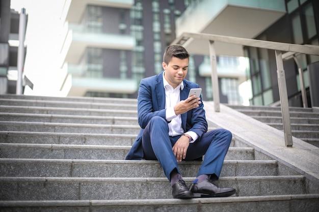 Homme d'affaires assis dans les escaliers dans la rue, vérifiant son téléphone intelligent