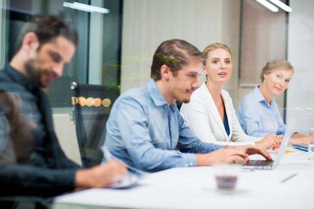 Homme d'affaires assis devant un ordinateur portable avec des collègues sur les côtés