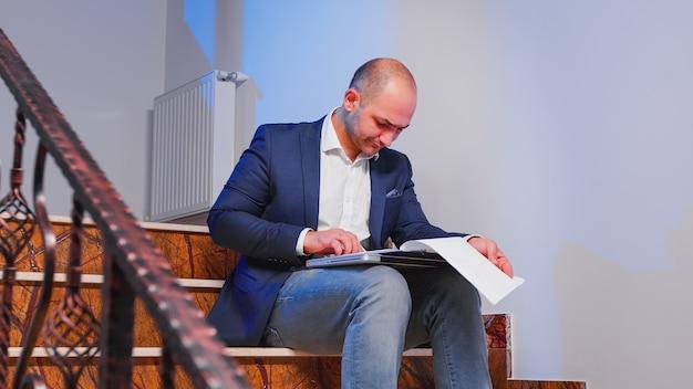 Homme d'affaires assis sur des escaliers dans un bâtiment d'entreprise analysant des documents du presse-papiers surmené dans une société financière. exécutif de bureau vérifiant les graphiques annuels finissant le projet de date limite d'entreprise