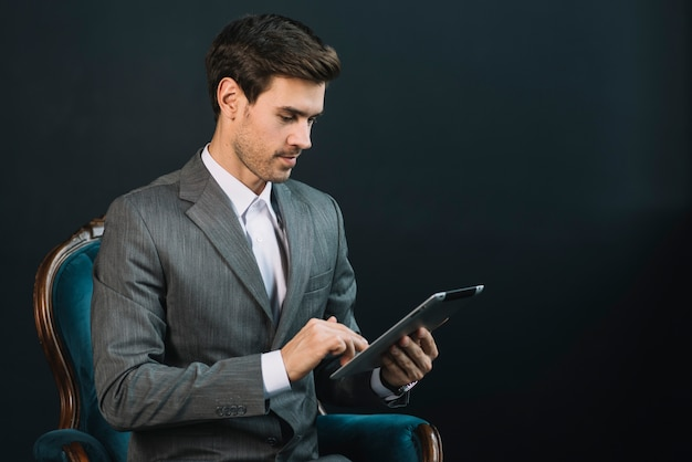 Homme d'affaires assis sur un fauteuil en costume à l'aide d'une tablette numérique sur fond noir