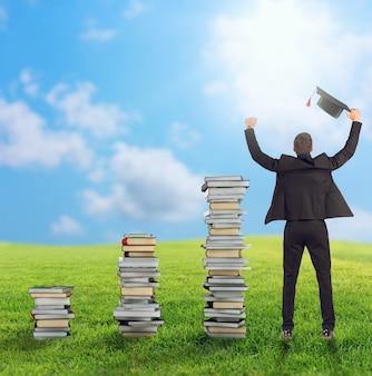Homme d'affaires assis sur une pile de livres avec chapeau de graduation