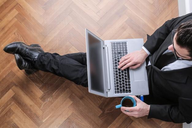 Homme d'affaires assis sur le sol avec un ordinateur portable