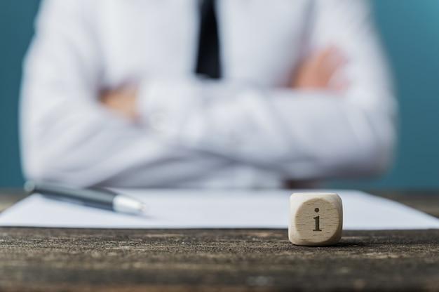 Homme d'affaires assis à son bureau avec un stylo et du papier devant lui et un dé avec la lettre i dessus
