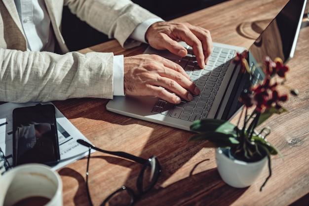 Homme d'affaires assis à son bureau et utilisant un ordinateur portable au bureau