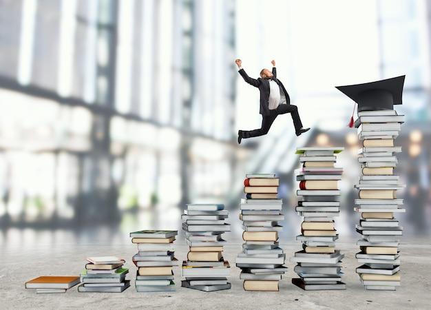 L'homme d'affaires atteint le chapeau de graduation sautant sur des piles de livres