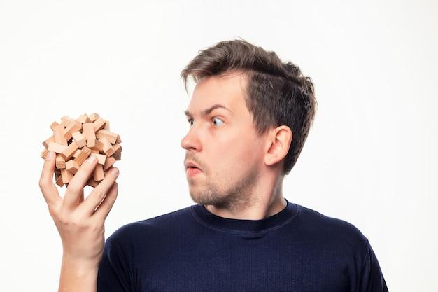 Homme d'affaires attrayant de 25 ans à la confusion au puzzle en bois.
