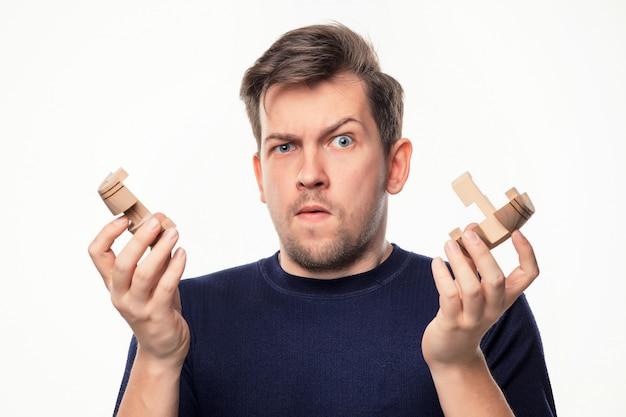 Homme d'affaires attrayant de 25 ans à la recherche de puzzle en bois.