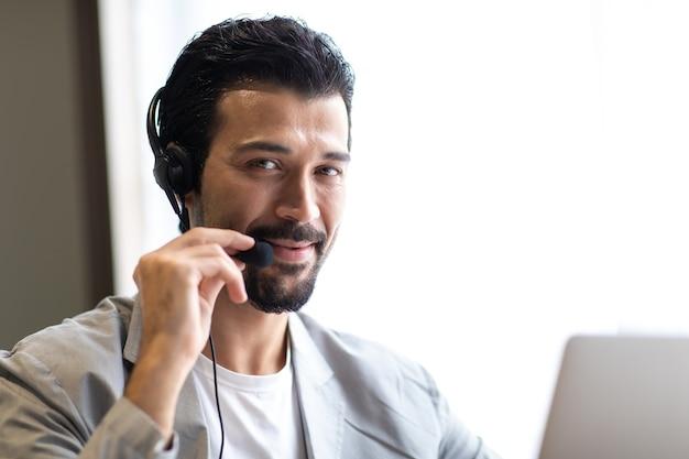 Homme d'affaires attrayant en costumes et casques souriant tout en travaillant sur le bureau