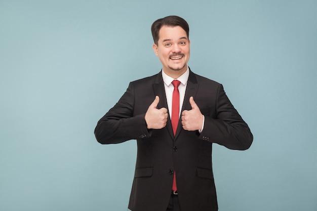 Homme d'affaires attrayant jeune adulte démontrer les pouces vers le haut comme signe