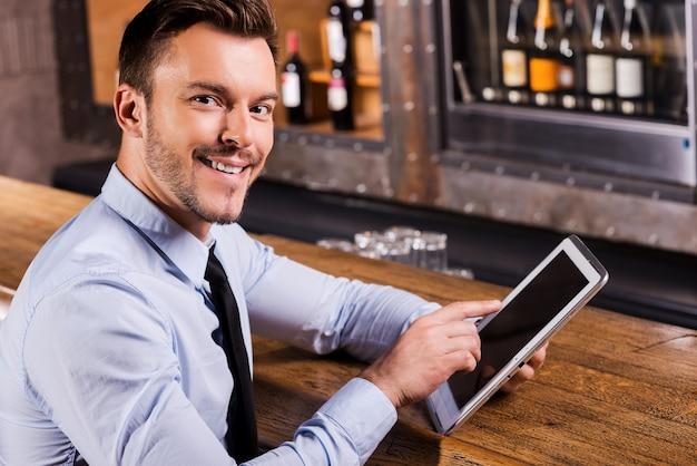 Homme d'affaires au bar. beau jeune homme en chemise et cravate travaillant sur tablette numérique et souriant assis au comptoir du bar