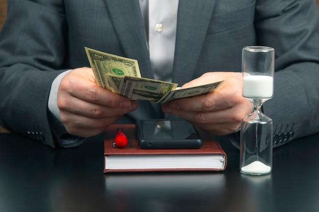L'homme d'affaires au bureau compte de l'argent sur fond de cadrans solaires. affaires et rémunération.