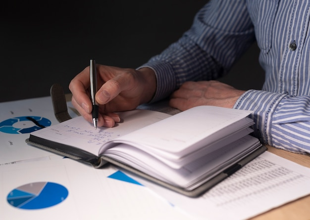 Homme d'affaires au bureau avec des documents financiers, préparation du rapport financier, analyse budgétaire dans les graphiques.