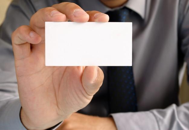 Homme d'affaires au bureau montre la carte de visite dans sa main