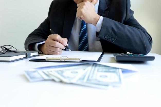 Homme d'affaires au bureau avec un paquet de factures