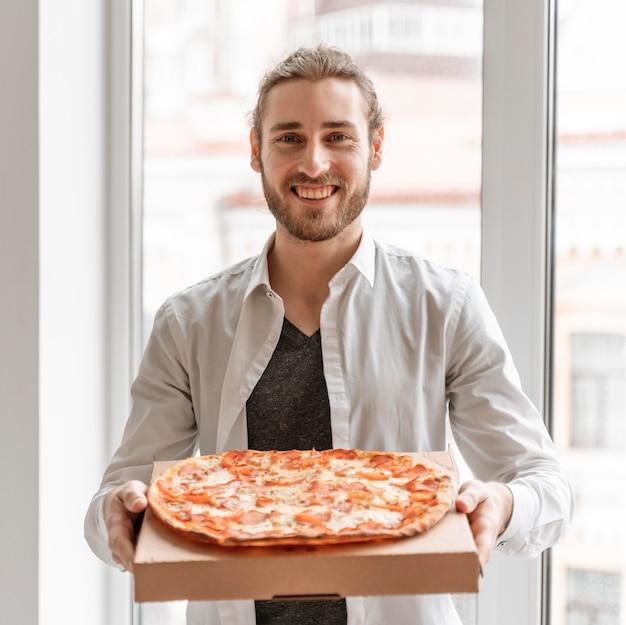Homme d'affaires au bureau avec pizza