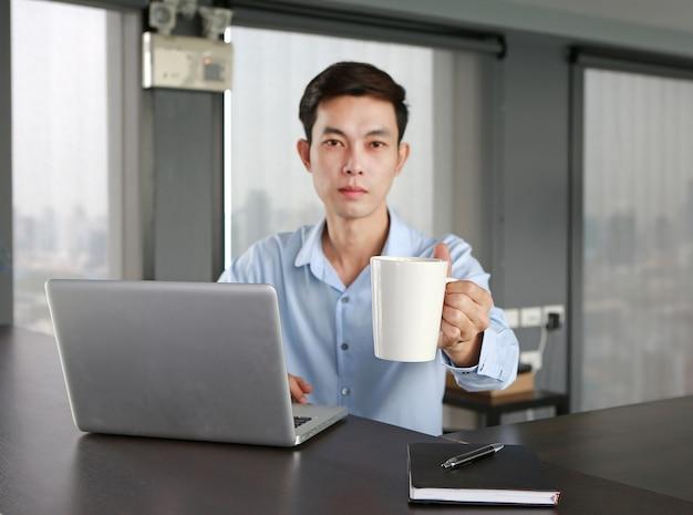 Homme d'affaires au lieu de travail offre une tasse de café