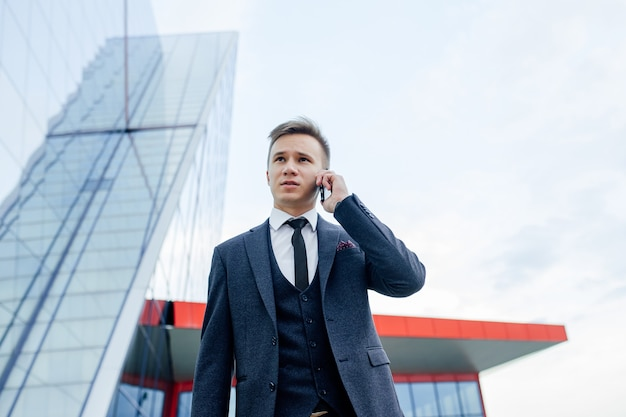 Homme d'affaires au téléphone dans un costume. homme d'affaires sur téléphone portable dans un costume marche appel exécutif actif dans la ville