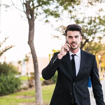 Homme d'affaires au téléphone dans le parc