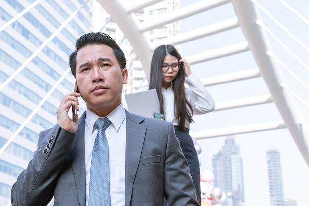 Homme d'affaires au téléphone, sa secrétaire marchant derrière