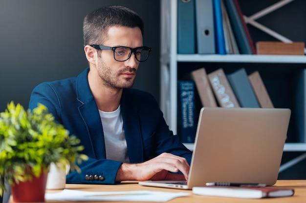Homme d'affaires au travail. jeune homme concentré travaillant sur un ordinateur portable alors qu'il était assis sur son lieu de travail au bureau