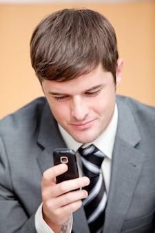 Homme d'affaires auto-assuré, écrire un message texte avec son téléphone portable