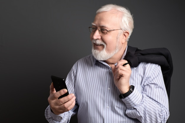Homme d'affaires aux cheveux grisonnant dans des verres avec un téléphone souriant amical