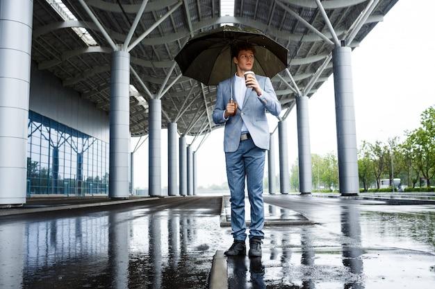 Homme d'affaires aux cheveux roux avec parapluie boire du café dans la rue