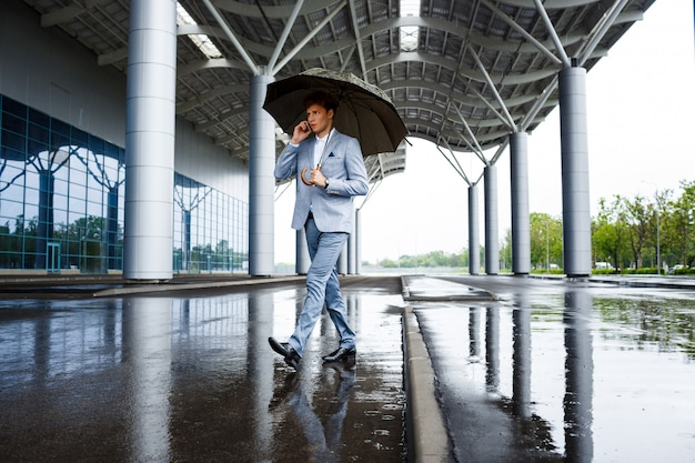 Homme d'affaires aux cheveux roux avec parapluie parler au téléphone
