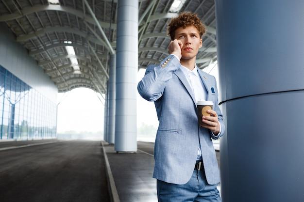 Homme d'affaires aux cheveux roux, parler au téléphone, tenant la tasse de café dans une main