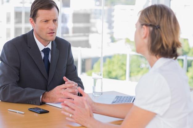 Homme d'affaires ayant une discussion avec un demandeur d'emploi