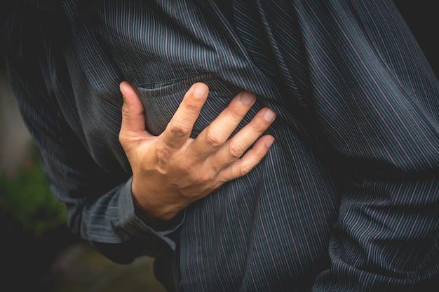 Homme d'affaires ayant des douleurs thoraciques et une crise cardiaque, la main tenant le douloureux.