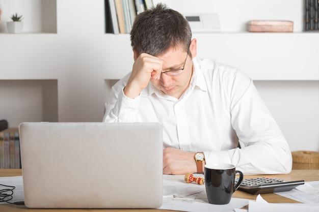 Homme d'affaires ayant le stress avec un ordinateur portable travaillant au bureau, homme de race blanche touchant sa tête, il a un mauvais concept de maux de tête, de stress et de surmenage.