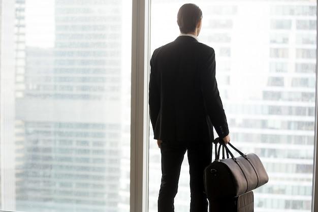 Homme d'affaires avec des bagages, debout devant une grande fenêtre.