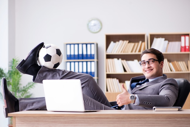 Homme d'affaires avec ballon de football au bureau
