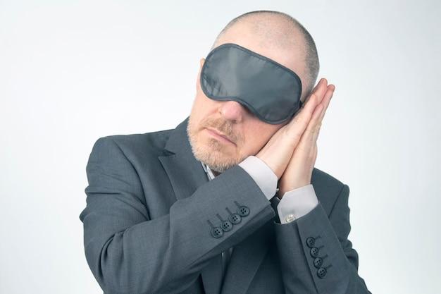 Homme d'affaires en bandeau pour dormir avec les bras levés pour se reposer sur un fond blanc