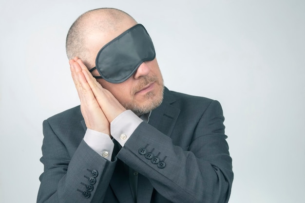Homme d'affaires en bandeau pour dormir avec les bras levés pour se reposer