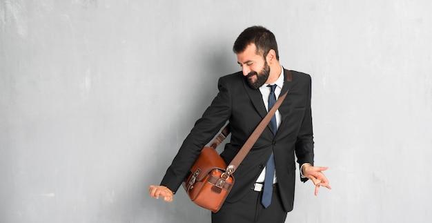 Homme d'affaires avec barbe, apprécier de danser tout en écoutant de la musique lors d'une fête