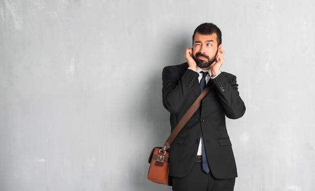 Homme d'affaires avec une barbe couvrant les oreilles avec les mains. expression frustrée