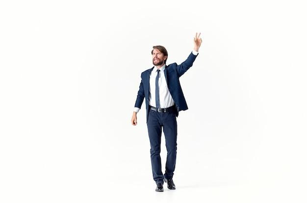Un homme d'affaires avec une barbe dans un costume classique fait des gestes avec ses mains sur un espace de copie léger.