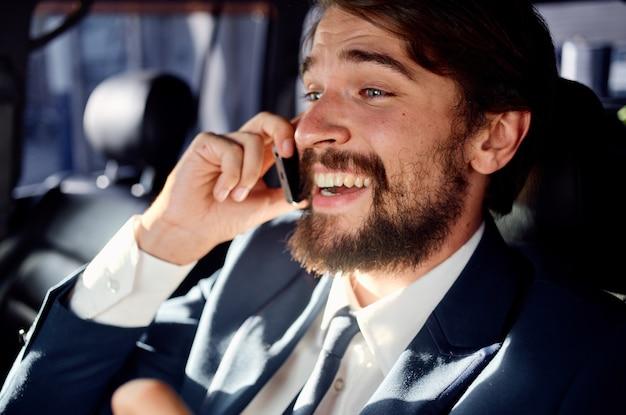 Homme d'affaires avec une barbe parlant au téléphone lors d'un voyage en voiture. photo de haute qualité